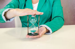 Hands holding hourglass. Two hands holding green sandglass Royalty Free Stock Photo