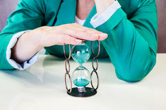 Hands holding hourglass. Two hands holding green sandglass Stock Photo