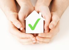 Hands holding house with check mark. Real estate and family home concept - male and female hands holding paper house with green check mark stock image