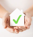 Hands holding house with check mark. Real estate and family home concept - hands holding paper house with green check mark stock photo