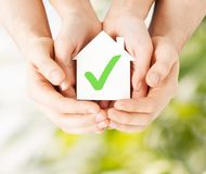Hands holding house with check mark. Real estate and family home concept - male and female hands holding paper house with green check mark stock images