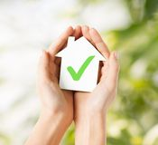 Hands holding house with check mark. Real estate and family home concept - hands holding paper house with green check mark royalty free stock images