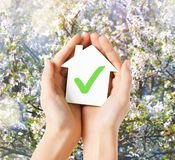Hands holding house with check mark. Real estate and family home concept - hands holding paper house with green check mark stock photos