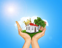Hands holding house on green grass with crown, red Stock Image