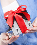 Hands holding house model with red bow Royalty Free Stock Photo