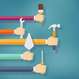 Hands holding housework and repair tools. Royalty Free Stock Image