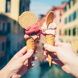 Hands holding ice cream in waffle cone. Woman`s and man`s hands holding italian ice cream in waffle cone on summer light royalty free stock photography