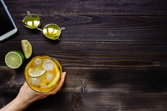 Hands holding ice drink. Ice tea, sunglasses and smartphone on the wooden table, top view. With copy space Royalty Free Stock Photography