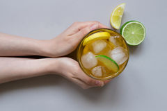 Hands holding ice drink with lemon and lime on the light blue background, top view Royalty Free Stock Photos