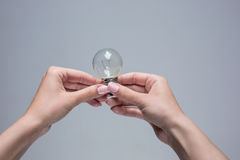 Hands holding an incandescent light bulb on gray background Royalty Free Stock Photos