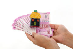 Hands holding Indian currency with house shape Royalty Free Stock Photo