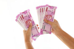Hands holding Indian 2000 rupee notes against white Royalty Free Stock Photography