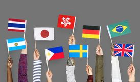 Hands holding international flags together royalty free stock photography