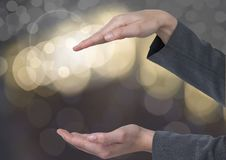 Hands holding invisible space with sparkling light bokeh background. Digital composite of Hands holding invisible space with sparkling light bokeh background royalty free stock photography