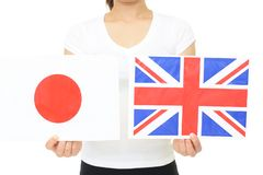 Japan and England national flag. Hands holding Japan and England national flag stock image