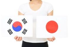 Japan and Korea national flag. Hands holding Japan and Korea national flag royalty free stock image