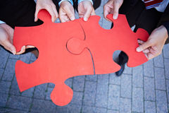 Hands holding jigsaw puzzle pieces. Many hands holding two red jigsaw puzzle pieces Stock Photo