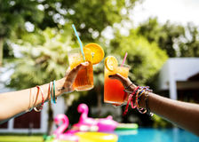 Hands holding juice glasses by the pool summer time Royalty Free Stock Photography