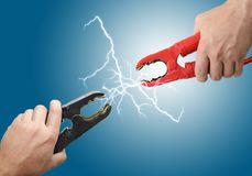 Power connection start. Hands holding jump start connectors with sparks between them Stock Images