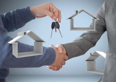 Hands Holding Keys With House Icons In Front Of Vignette With Handshake Stock Image