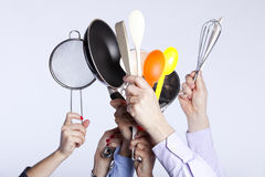 Hands holding kitchenware tools. Group of people hands holding some kitchenware tools (selective focus Stock Image