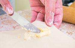 Hands holding knife spreading fresh butter on pastry - close view Stock Image