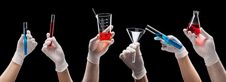 Hands holding laboratory glassware with liquids Stock Photos