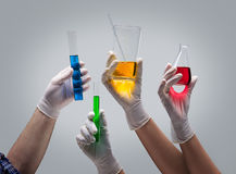 Hands holding laboratory glassware with liquids Stock Images