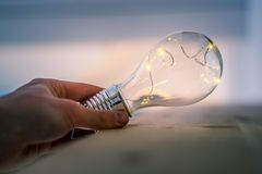Time for ideas, inspiration and invention: Hands are holding a LED lightbulb. Hands are holding a LED lightbulb over the wooden floor. Symbol for ideas and royalty free stock photography