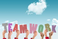hands holding letters teamwork on sky background Stock Photos