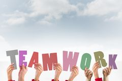 hands holding letters teamwork on sky background Stock Image