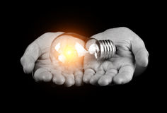Hands holding light bulb. Isolated on black Royalty Free Stock Photos