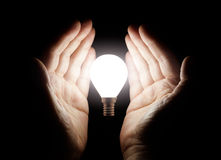 Hands holding light bulb Stock Images