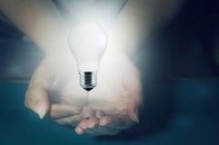 Hands holding a light bulb turned