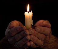 Hands holding lighted candle in darkness. Strong hands cupped around a lighted candle with dark background. Could illustrate many abstract concepts: hope, belief Royalty Free Stock Photos
