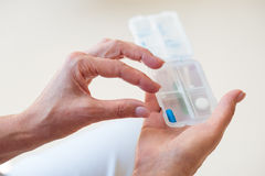 Hands holding little box with medicals. Health. Close up of female hands holding little box with different pills Royalty Free Stock Image