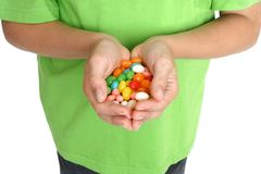 Hands holding lollies. Child's hands holding a handful of lollies Royalty Free Stock Images