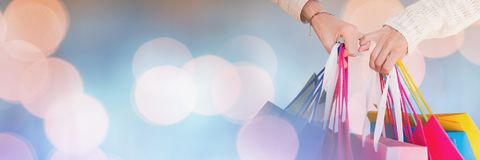 Hands holding lots of Shopping bags with sparkling lights bokeh transition stock photo