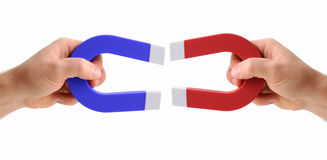 Hands holding magnets one red and one blue. Isolated on a white background Royalty Free Stock Photography