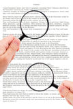 Hands holding magnifying glass reading document Stock Images