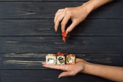 Hands holding sushi and raspberry ginger 2 Royalty Free Stock Photography