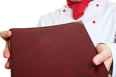 Hands holding menu card. Hands of a chef cook holding menu card Stock Image