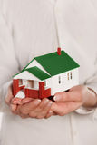 Hands holding miniature house. Miniature model house in human hands Stock Photo