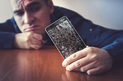 Hands holding a mobile phone with a broken screen over the wooden surface. A man looks at his broken phone lying on a wooden table with a sad look. guy was stock images