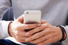 Hands holding a mobile phone. Closeup of a young man's hands holding a mobile phone with the lens aperture visible on the top left corner of the device Stock Photography