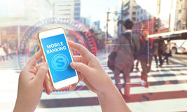 Hands holding mobile phone with Mobile banking. Mixed with business graphic background Royalty Free Stock Images