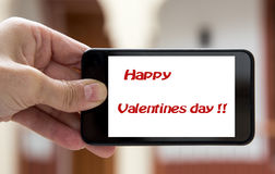 Hands holding mobile phone with sign valentines day Royalty Free Stock Images