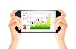 Hands holding mobile phone with stock market chart isolated over Stock Images