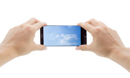 Hands holding mobile smart phone with sky in screen. Stock Photos
