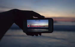 Hands holding mobile smart phone and take a video of the sunset in summer time Royalty Free Stock Images